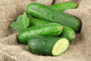 Tasty green cucumbers on sackcloth background